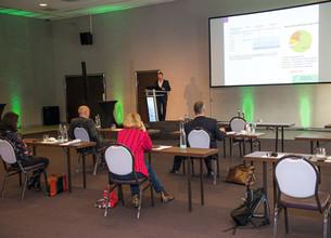 Aufnahme des Präsentationssaales mit Blick nach vorne auf die Teilnehmer und Präsentationsleinwand
