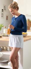 Una mujer con un vendaje de tórax azul oscuro está en la cocina con un vaso de zumo de naranja en la mano