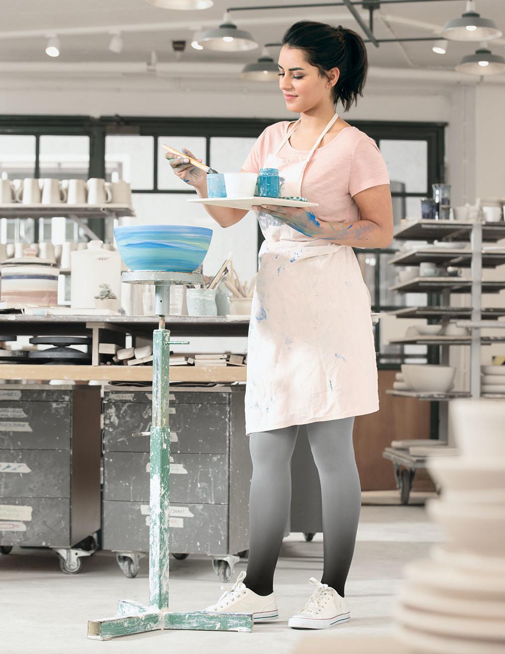 Una donna osserva dei vassoi in argilla indossando calze compressive Juzo Inspiration in Dip Dye colore Mirtillo