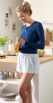 Frau mit dunkelblauer Thorax-Bandage steht in der Küche und hält ein Glas Orangensaft in der Hand