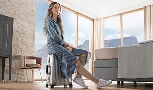 Frau sitzt auf ihrem Koffer mit Reisestrümpfen