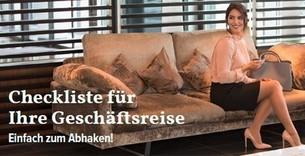 Frau im Businessoutfit wartet mit Koffer im Hotel