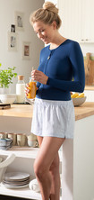 A woman with a dark blue thorax support stands in a kitchen with a glass of orange juice in her hand
