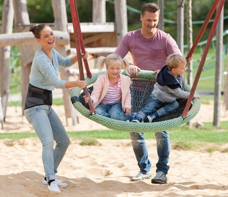 Familie auf dem Spielplatz, Mutter trägt Juzo Lumbal