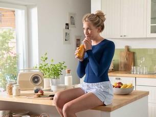 Frau mit blauer Thoraxbandage sitzt auf einer Küchentheke und trinkt  ein Glas Orangensaft