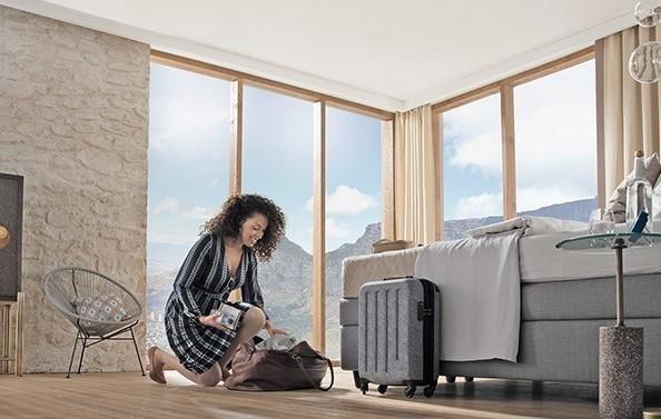 Frau packt Reisetasche im Hotelzimmer aus