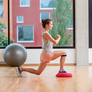 A woman doing a lunge, lowering her back leg to just above the ground