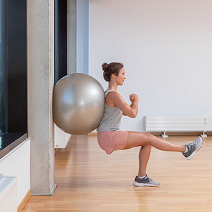 A woman leaning against a wall with an exercise ball, doing a squat with one leg extended