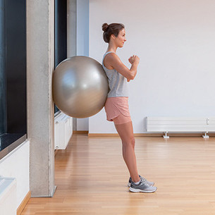 A woman leaning upright against a wall with an exercise ball