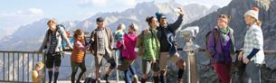 Ludzie w odzieży uciskowej delektują się podziwiają górski widok