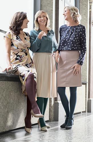 Drei Frauen stehen zusammen und lachen