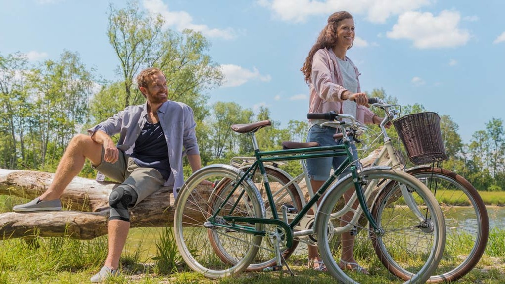 Mann und Frau mit Fahrrädern am Ufer eines Sees