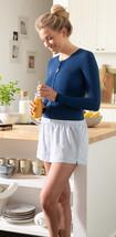 Femme portant un bandage thoracique bleu foncé dans la cuisine, un jus d'orange à la main