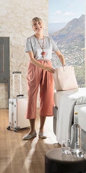 Kvinna som packar upp väskorna på hotellrummet efter en lång resa
