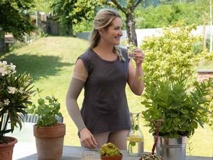 Frau im Garten trägt einen Kompressionsaermel und trinkt ein Glas Wasser