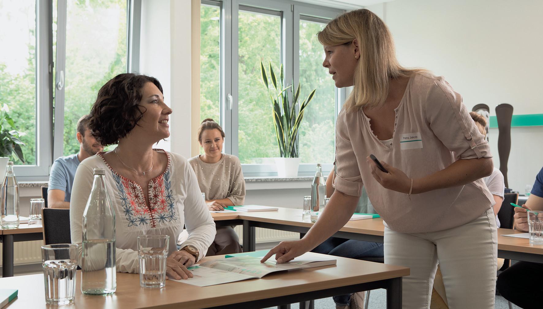 Zwei Frauen unterhalten sich in einem Seminar