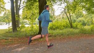 Mann joggt durch Wald und trägt ein Patellasehnenband