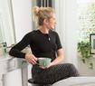 Femme portant un bandage thoracique noir assise à sa coiffeuse, une tasse de thé à la main