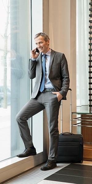 Affärsman iklädd resestrumpor talar i telefon