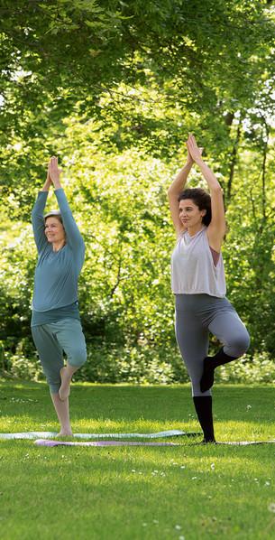 Vrouwen beoefenen yoga in het park met Juzo Move