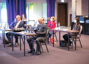 Präsenz-Teilnehmer des 7. Narbensymposiums sitzen an Einzeltischen im Präsentationssaal