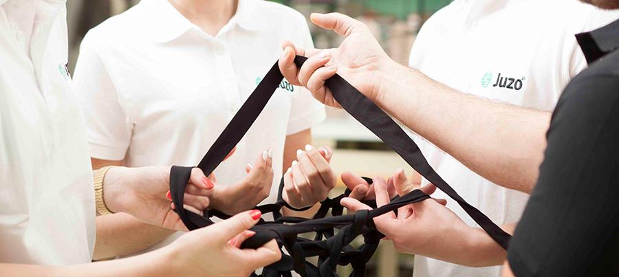 Vier Personen mit Fäden zwischen sich gespannt