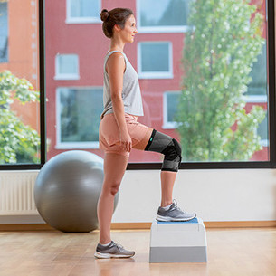 A woman putting her right leg on an aerobics step