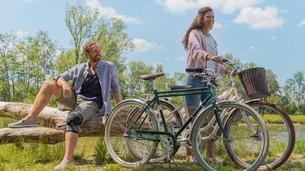 Mężczyzna i kobieta z rowerami nad brzegiem jeziora