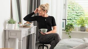 Mulher com camisola compressiva preta sentada num toucador com uma chávena de chá na mão