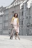 Vrouw wandelt met fiets door de straat en draagt Juzo Inspiration