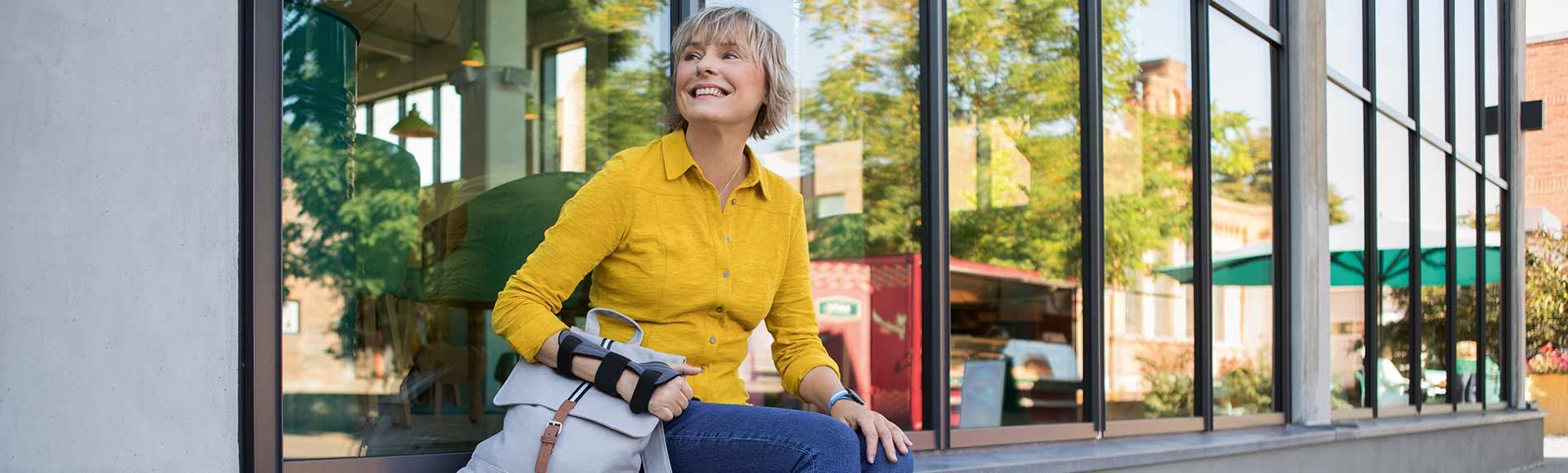 Frau mit Handgelenkbandage JuzoPro Manu Xtec Palmar sitzt vor einer Glasfassade und blickt lächelnd in die Ferne