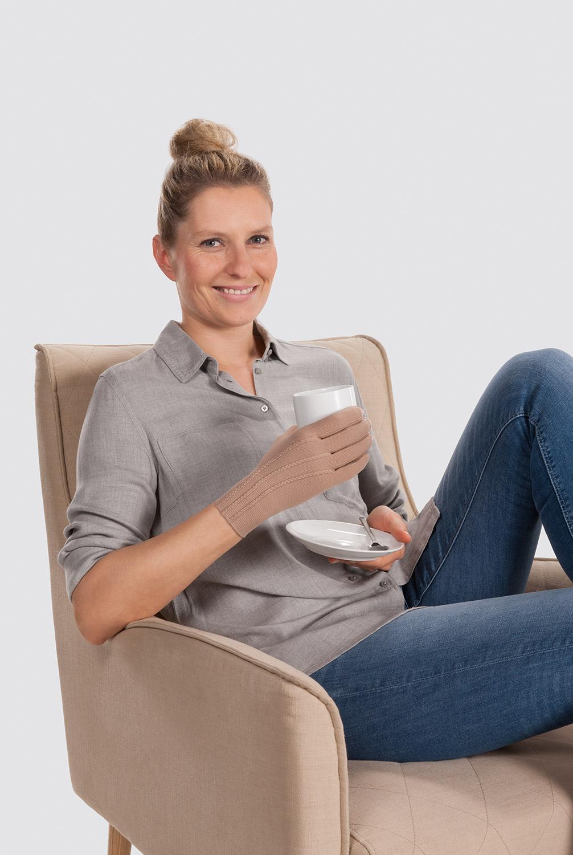 Frau mit Kompressionshandschuh trinkt Milch