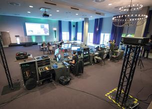 Aufnahme des Präsentationssaales mit Technik, Teilnehmern und Bühne