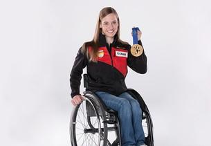 Anna Schaffelhuber sentada en la silla de ruedas, con una medalla en la mano