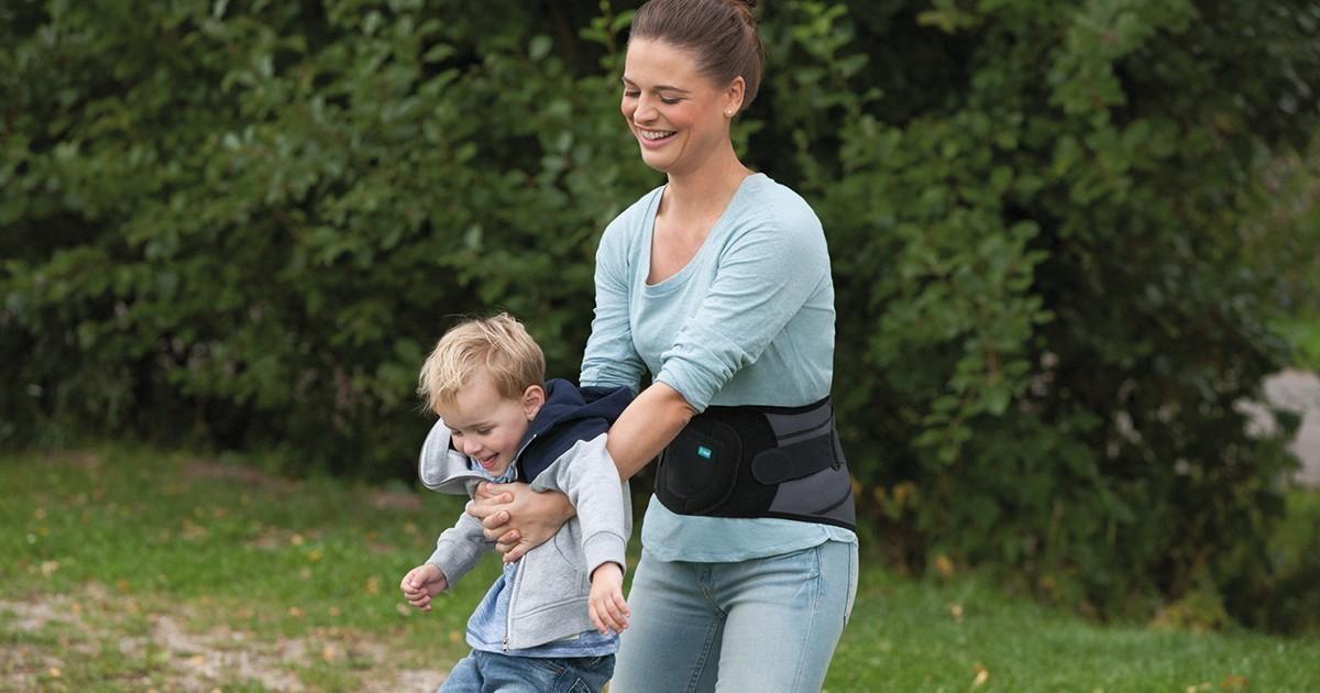 Frau mit JuzoPro Lumbal trägt Kind