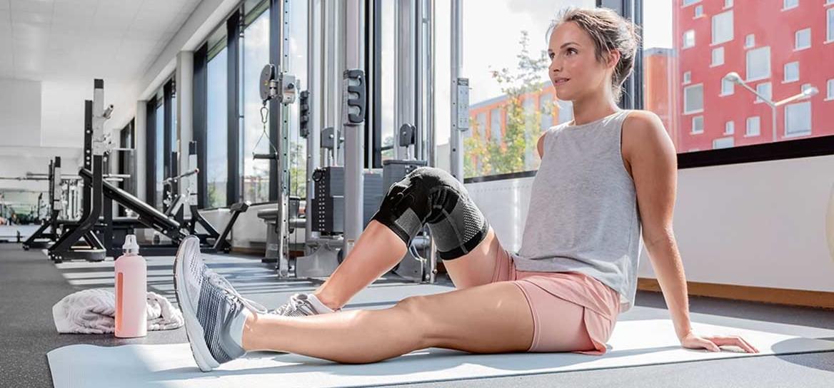 Frau sitzt auf einer Trainingsmatte und trägt eine Knieorthese