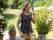 Une femme dans le jardin porte un manchon de compression et boit un verre d'eau