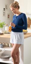 Vrouw met donkerblauwe thoraxbandage staat in de keuken en heeft een glas sinaasappelsap in haar hand
