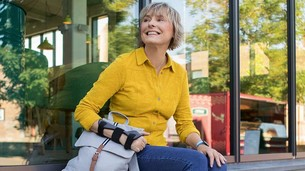Kobieta ze stabilizatorem miękkim nadgarstka JuzoPro Manu Xtec Palmar siedzi przed szklaną fasadą i patrzy z uśmiechem w dal