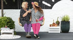 Vriendinnen zitten op een schommel in hun compressiekleding in Pink Soul en Violet Truth