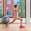 A woman doing a lunge forwards on a soft cushion