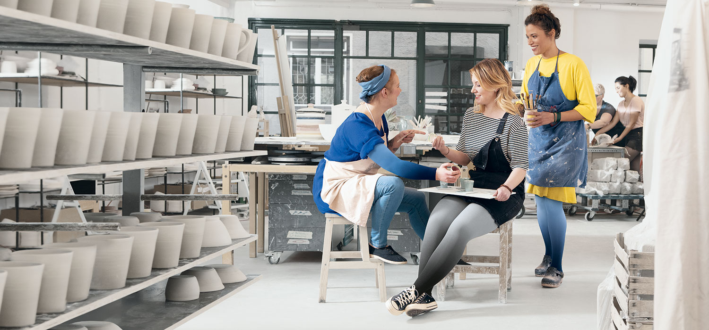 Zwei Frauen sitzen auf Tisch und tragen Kompressionsstrümpfe in Dip Dye