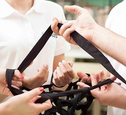 vier Personen die mit den Händen Stricken