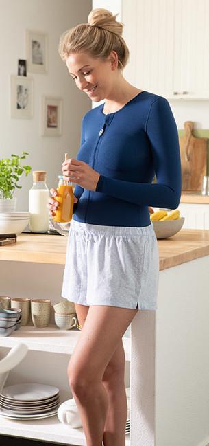 Mulher com camisola compressiva azul escura em pé na cozinha e com um copo de sumo de laranja na mão