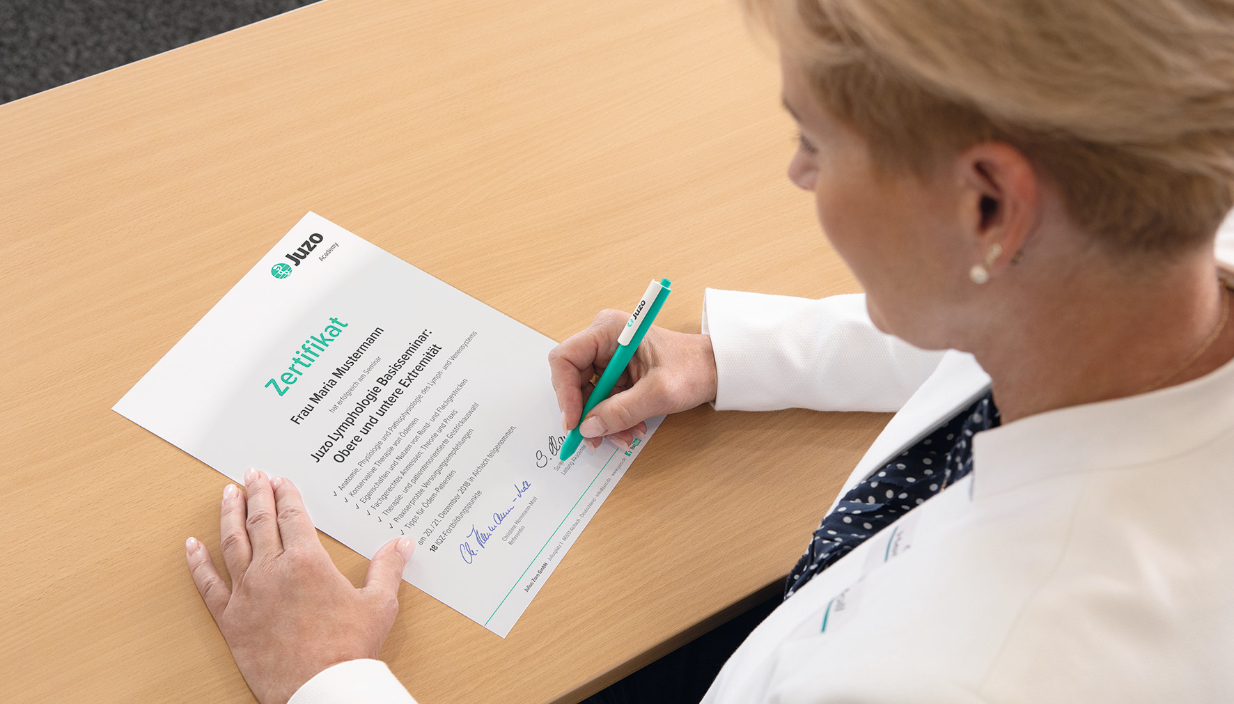 Referentin unterschreibt Zertifikat