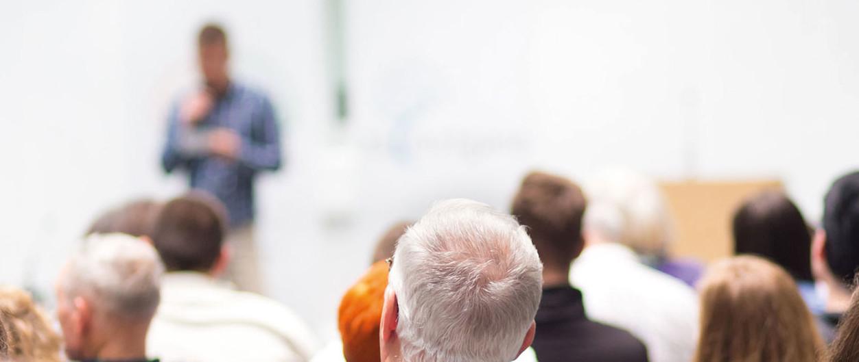 Mann sitzt im Publikum eines Symposiums