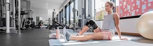 Frau trägt Orthese im Fitness-Studio
