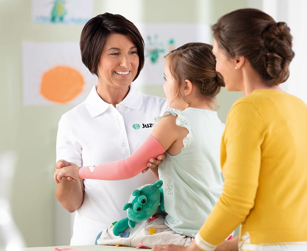 Frau vom Sanitätshaus begutachtet Kompression am Kind