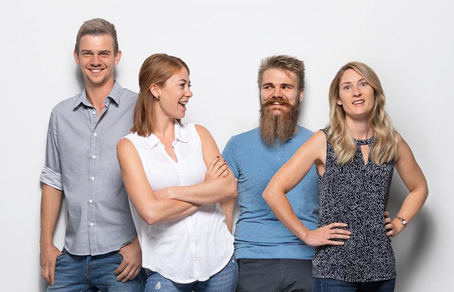 Vier junge Menschen lehnen sich aneinander an