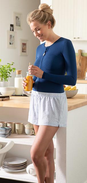 Kvinna med mörkblått thoraxbandage står i köket och håller ett glas apelsinjuice i handen